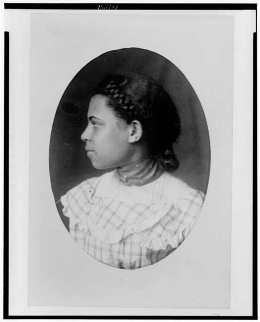 [African American girl with braided hair, head-and-shoulders portrait, facing left]