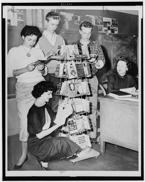 [Connie Masi, Sheila Macy (kneeling), Ernest Sims, and Fred Kimtscher students at William Cullen Bryant High School gather around mobile shelving in the library]