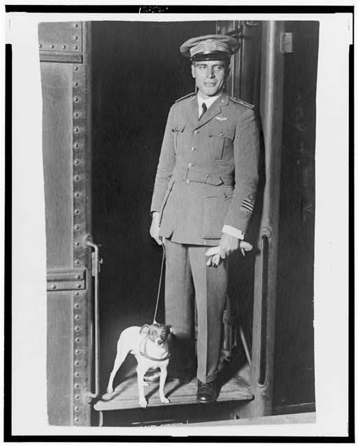 [Umberto Nobile, full-length portrait, dressed in military uniform standing in a doorway with his dog, Titina]