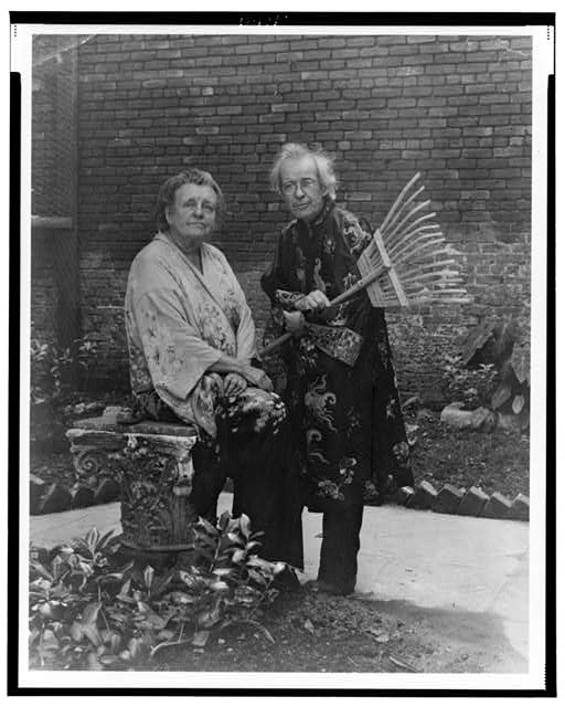 "[Frances B. Johnston in garden in New Orleans with ""Pops"" Whitesell, who is holding a rake]"