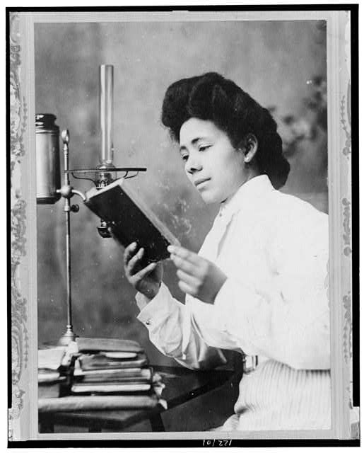 [African American woman, half-length portrait, facing left, reading book]