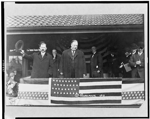 [William Howard Taft, standing on stand, facing right, with other men]