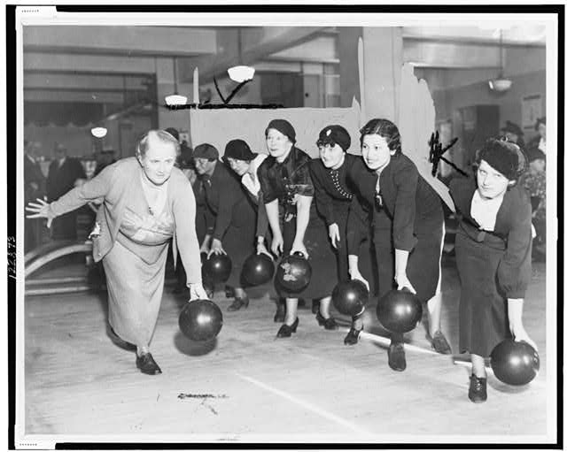 [Floretta McCutcheon demonstrates the proper way to hold a bowling ball as eager students look on]