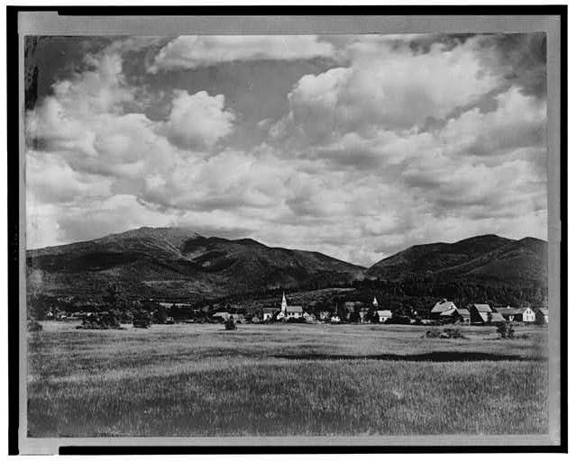 [View across meadow of town (Franconia?) with hills in the background]