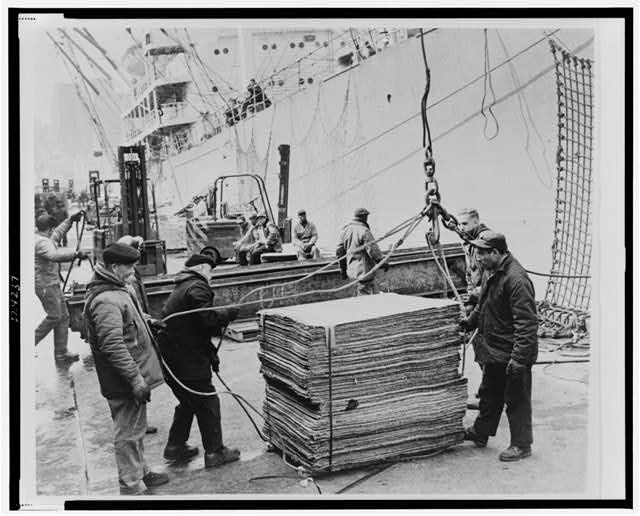 [Longshoremen loading cargo onto a ship at Port Authority Piers, Furman St., Brooklyn, New York]