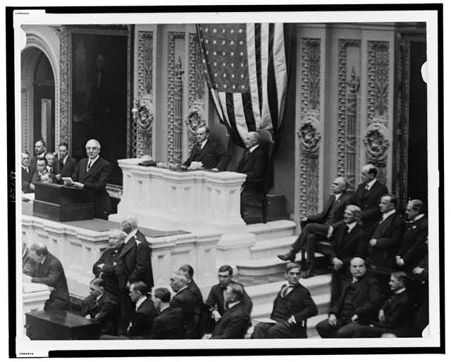 [A session in the House of Representatives, with Warren Harding speaking, and Calvin Coolidge and Frederick Gillett seated behind desk]