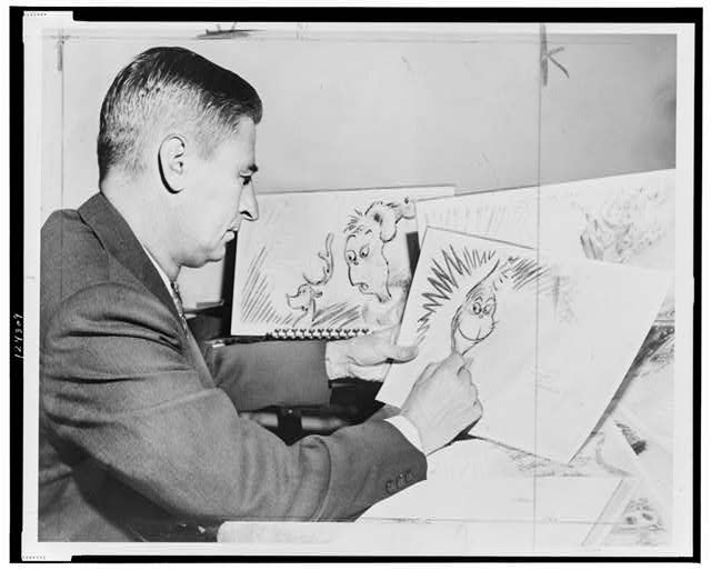 "Dr. Seuss (Ted Geisel) at work on a drawing of a grinch, the hero of his forthcoming book, ""How the Grinch Stole Christmas"""