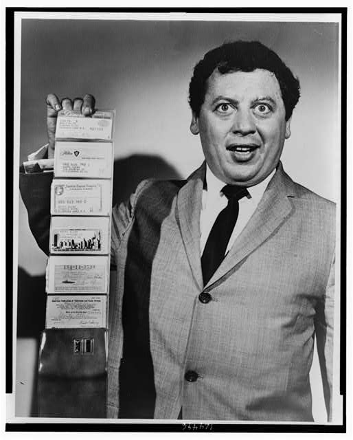 [Marty Allen, half-length portrait, holding wallet with six credit cards extended in accordion fashion]