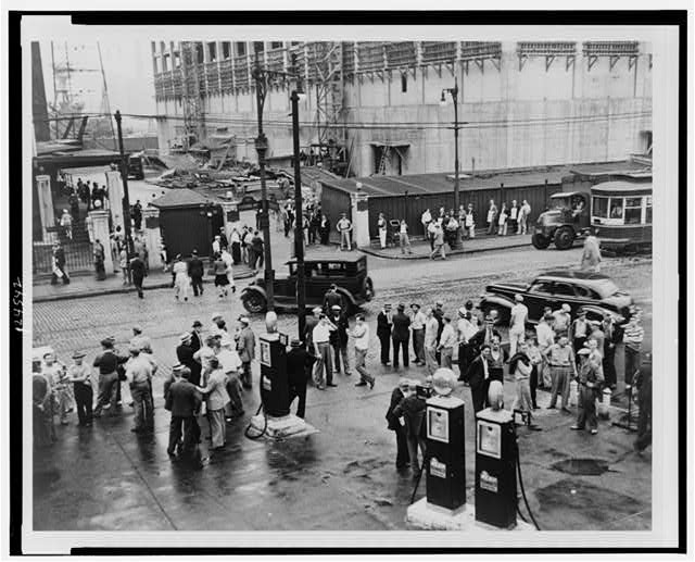 [Men milling around street across from the Brooklyn Navy Yard during an electrical workers strike; in background is a picket line]