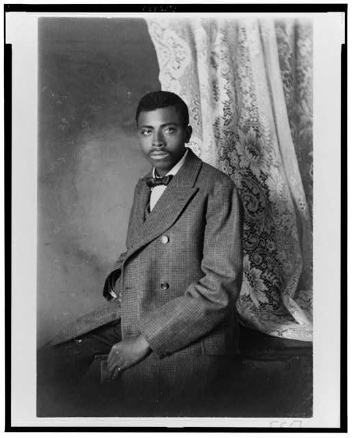 [African American man, three-quarter length portrait, seated, facing left]