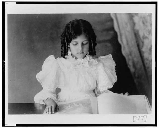 [African American girl, half-length portrait, looking at open book]
