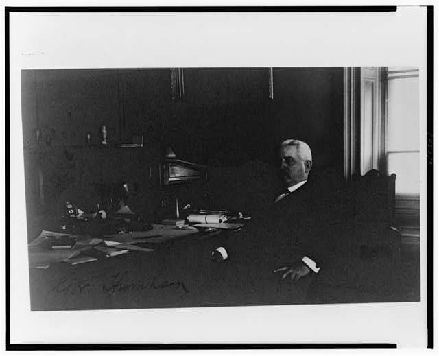 [Gov. Thompson(?), Treasury Department employee, half-length portrait, seated at desk, facing left]