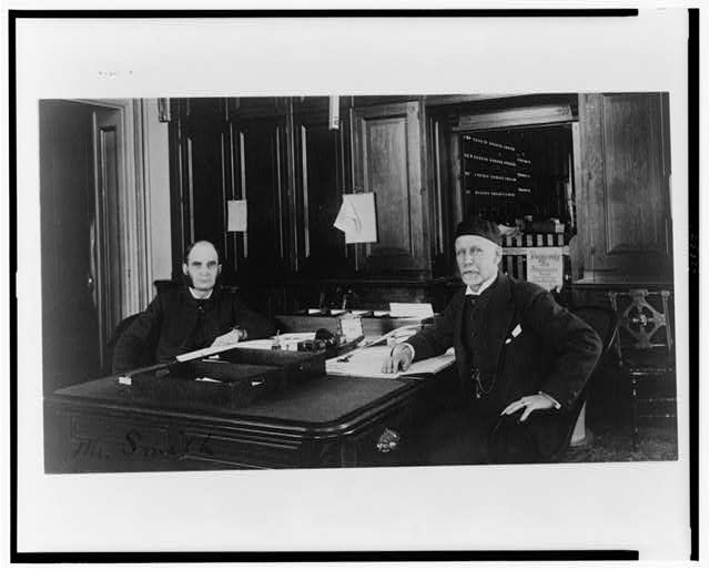 [Two Treasury Department employees seated at desk in office]