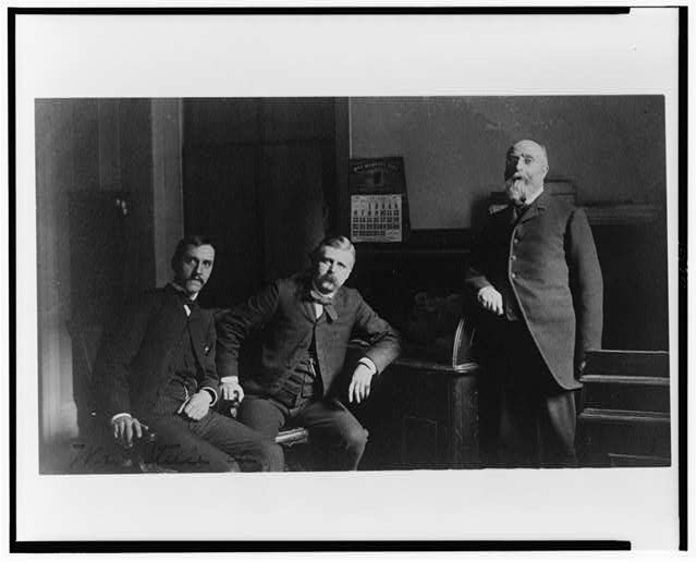 [Three Treasury Department employees, Mr. Steele(?) and two other men, posed in office]