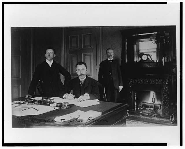 [Three Treasury Department employees, Mr. Graham, John Brown, and another man, posed in an office with a fireplace]
