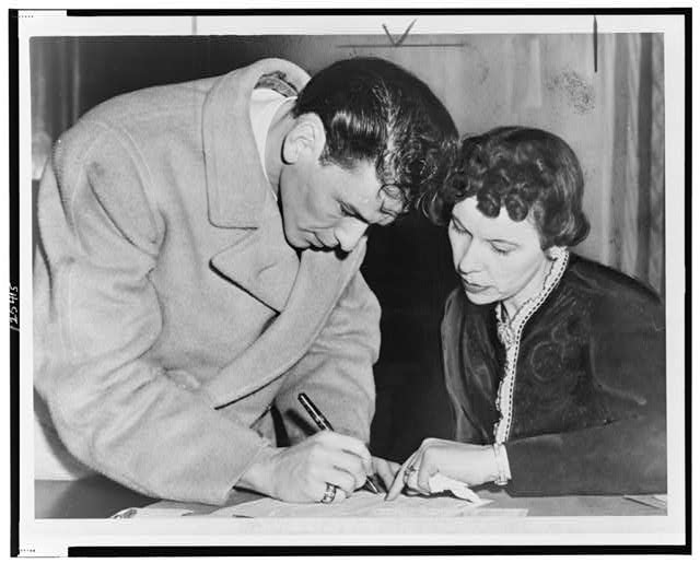 Frank Sinatra signs his induction papers while Chief Clerk Mrs. Mae E. Jones helps out at local board No. 19-160 Danforth St., Jersey City