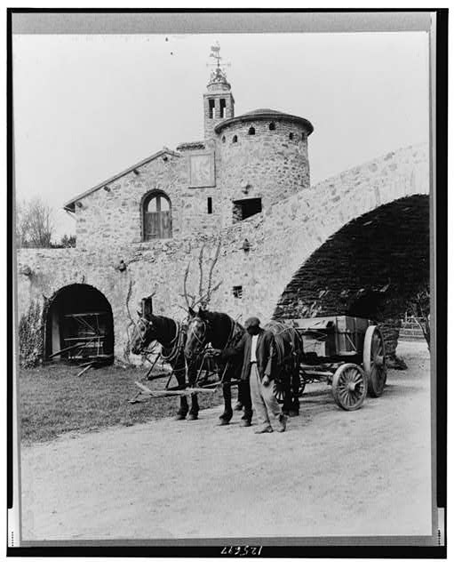 "[""Surprise Valley Farm,"" Arthur Curtiss James property, Beacon Hill Road, Newport, Rhode Island. Courtyard with wagon and team and African American workman]"
