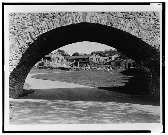 "[""Surprise Valley Farm,"" Arthur Curtiss James property, Beacon Hill Road, Newport, Rhode Island. Stone cottages through archway]"