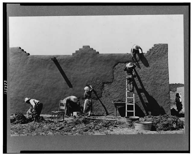Spanish-American women replastering an adobe house. This is done once a year. Chamisal, New Mexico