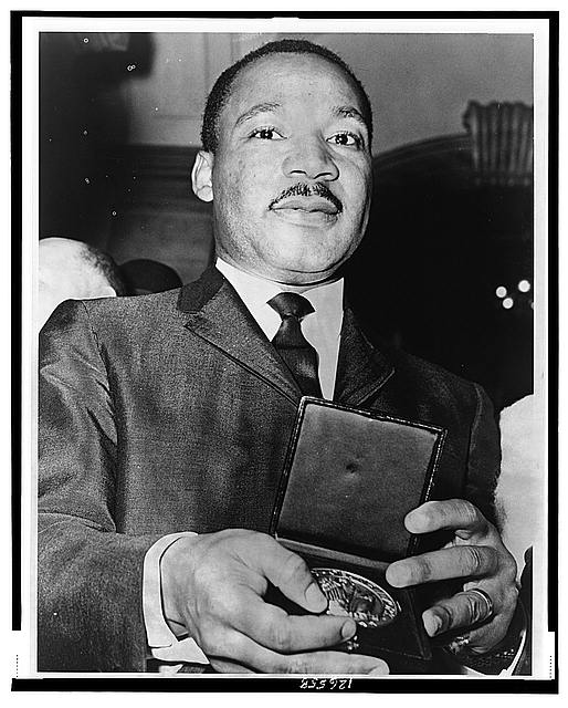 Dr. Martin Luther King showing his medallion received from Mayor Wagner