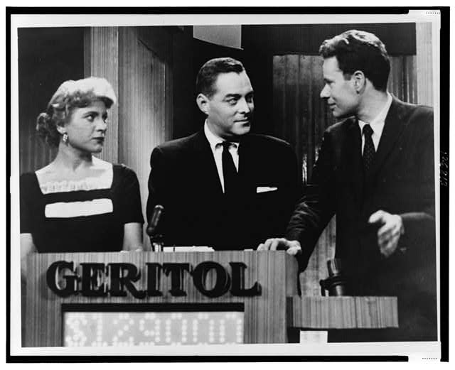 "[Quiz show ""21"" host Jack Barry turns toward contestant Charles Van Doren as fellow contestant Vivienne Nearine looks on]"