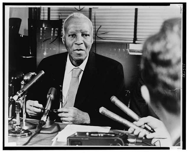 [A. Philip Randolph, half-length portrait, seated behind microphones on desk, facing front, at press conference]