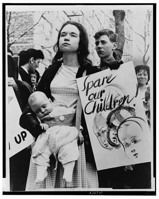 Little Denise Davidson, 5 months old, sleeps peacefully while her mother, Mrs. Donald Davidson, of 278 Clinton St., Bklyn., marches with ban-the-bomb group outside the United Nations to protest resumption of A-[bomb] tests by the United States