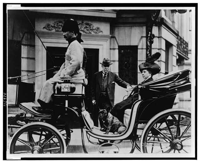 Ambassador George Bakhmeteff standing alongside carriage on which his wife is seated, with dog