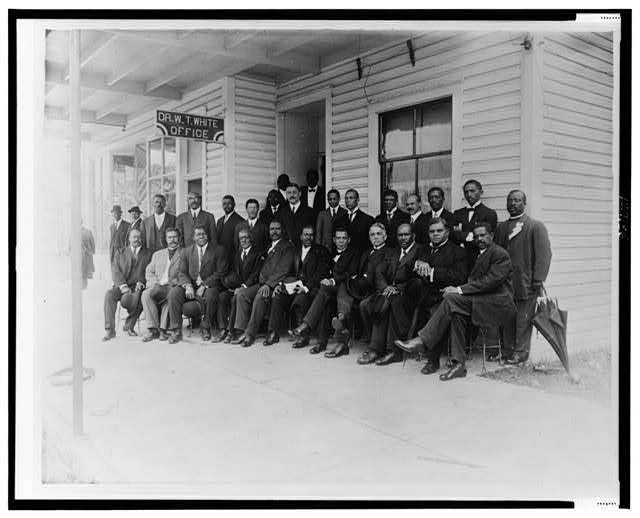 [Booker T. Washington seated with group of men outside the office of Dr. W.T. White, in Palatka, Florida]