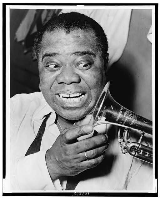 [Louis Armstrong, head-and-shoulders portrait, facing front, looking at trumpet]