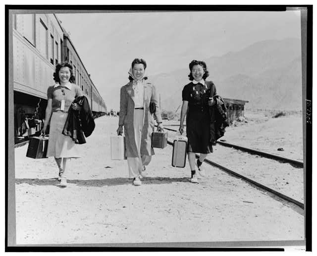 Lone Pine, Calif. May 1942--Three Japanese-American girls with suitcases, who have just arrived by train from Elk Grove and who will be transported by bus from Lone Pine to Manzanar, a war relocation authority center where they will remain for the duration of war