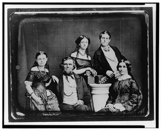 [Benjamin family group portrait, posed around a column]