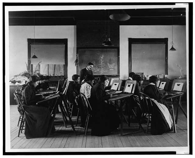 [Group portrait of teacher and students at Hampton Institute painting watercolor pictures of butterflies]