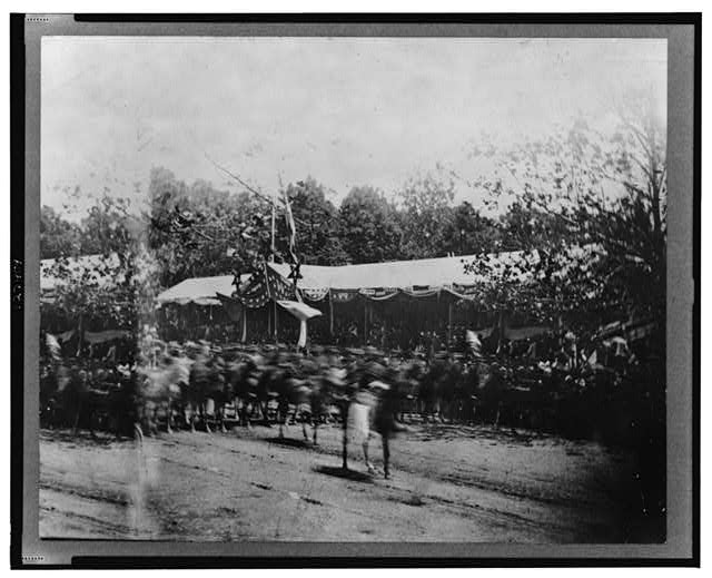 "[Mounted cavalry riding past reviewing stand during the ""grand review"" of the Union Army, Washington, D.C.]"