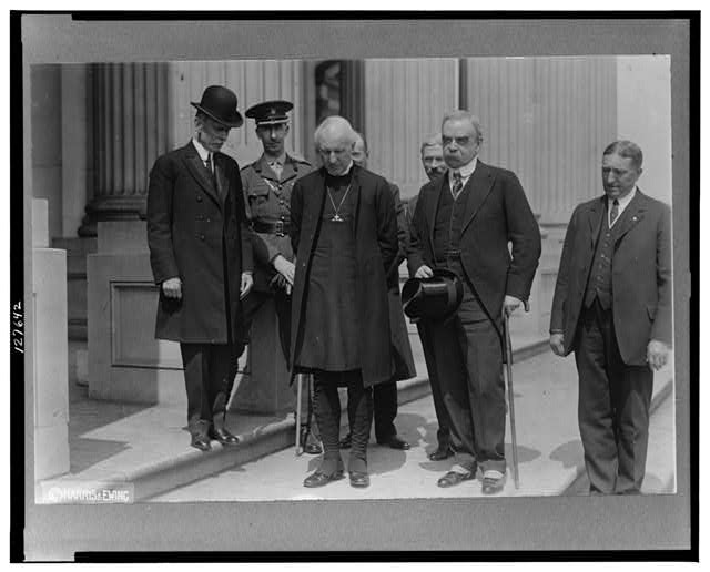[Cosmo Gordon Lang, Archbishop of York, Major Crawford Stuart and five others, full-length portrait standing on sidewalk]