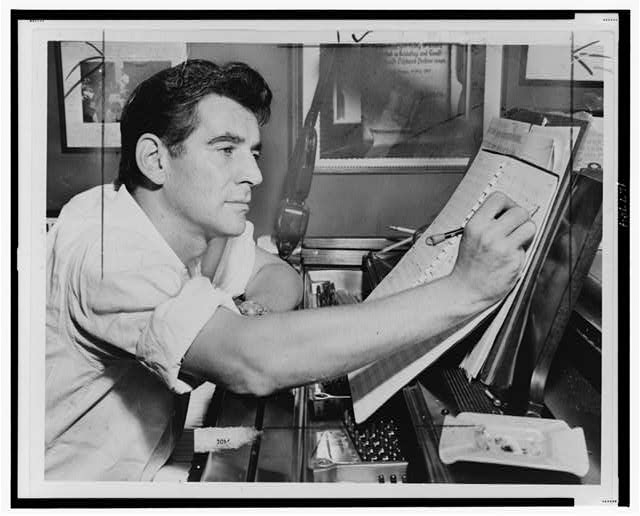 [Leonard Bernstein, half-length portrait, facing right, seated at piano, making annotations to musical score]