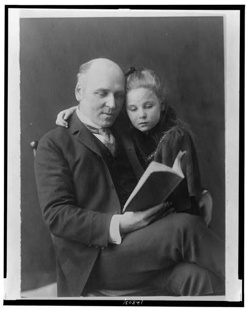 [Howard Pyle, three-quarter length portrait, seated, facing slightly right, looking at book, and his daughter Phoebe with arm around his shoulders]