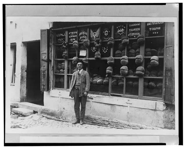 "[Baker standing in front of the ""American Bakery"" which displays signs in Armenian, Ladino (in Hebrew characters), English, Ottoman Turkish, Greek and Russian with samples of bread attached to the mullions, Ortaköy, Istanbul, Turkey]"