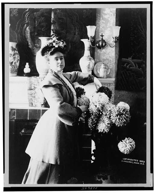 [Mrs. Adna R. Chaffee, three-quarter length portrait, standing in front of fireplace, facing slightly right, with floral arrangement on the right]