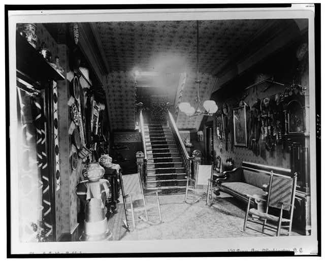 [Stairhall in John Alexander Logan home showing Native American pottery, baskets, textiles, and other items, Washington, D.C.]