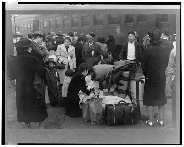 Los Angeles, California. Japanese-American evacuation from West Coast areas under U.S. Army war emergency order. Waiting with their luggage at the old Santa Fe station for a train to take them to Owens Valley