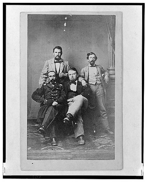 [Four unidentified men including at least one Union officer, full-length portrait, seated and standing, facing front]