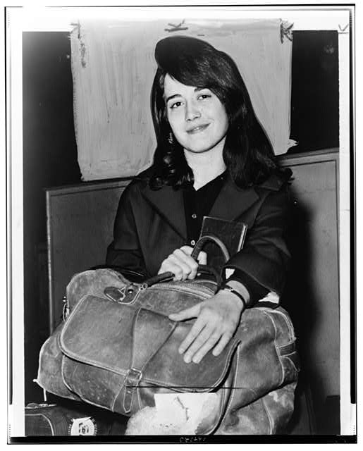 [Martha Argerich, full-length portrait, facing front, seated, holding luggage, at Pier 86, after having arrived on the liner Constitution]