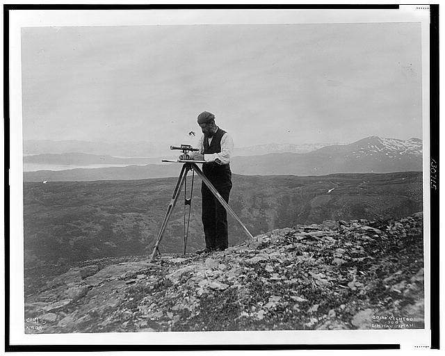 Surveyor with theodolite(?) in the mountains of Alaska