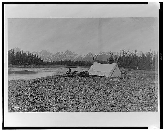 [A man, possibly B.E. Fernow, seated next to river, tent on the right, mountains in background, Alaska, 1899]
