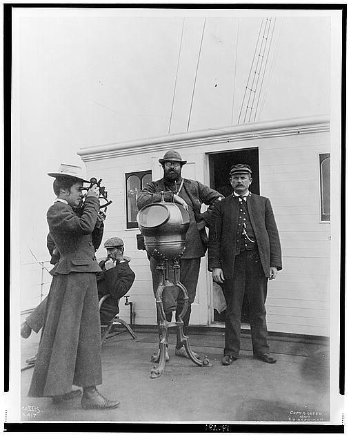 [Woman looking through sextant on board the expedition vessel, George W. Elder, with two men and Capt. Peter Doran during Harriman expedition to Alaska, 1899]