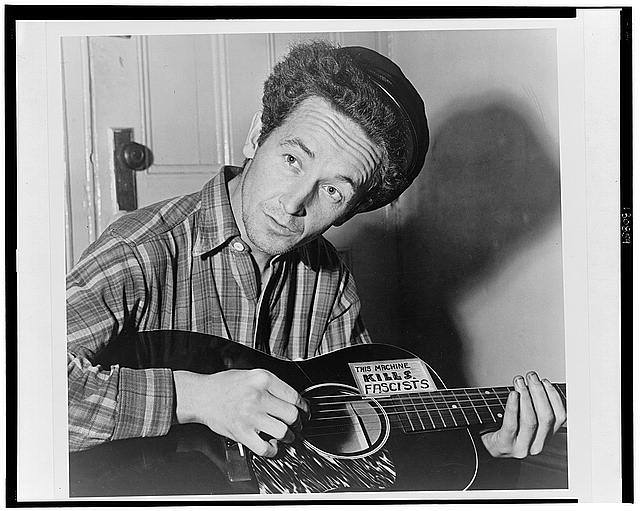 [Woody Guthrie, half-length portrait, seated, facing front, playing a guitar that has a sticker attached reading: This Machine Kills Fascists]