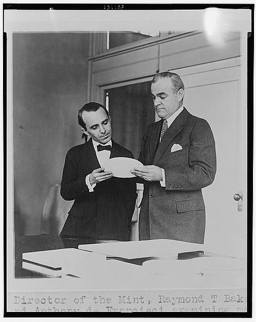 Director of the Mint, Raymond T. Baker, and Anthony de Francisci examining model of new silver dollar, the first of which will be issued by Jan. 1st