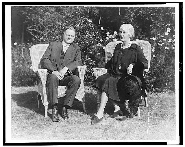 [Herbert Hoover and Mrs. Hoover, full-length portrait, seated on wicker chairs, facing front]
