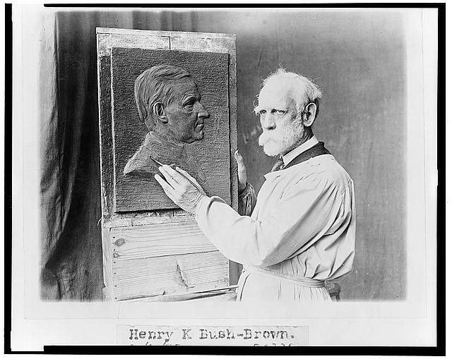 [Henry K. Bush-Brown, half-length portrait, wearing smock and working on his bas-relief portrait of Calvin Coolidge]
